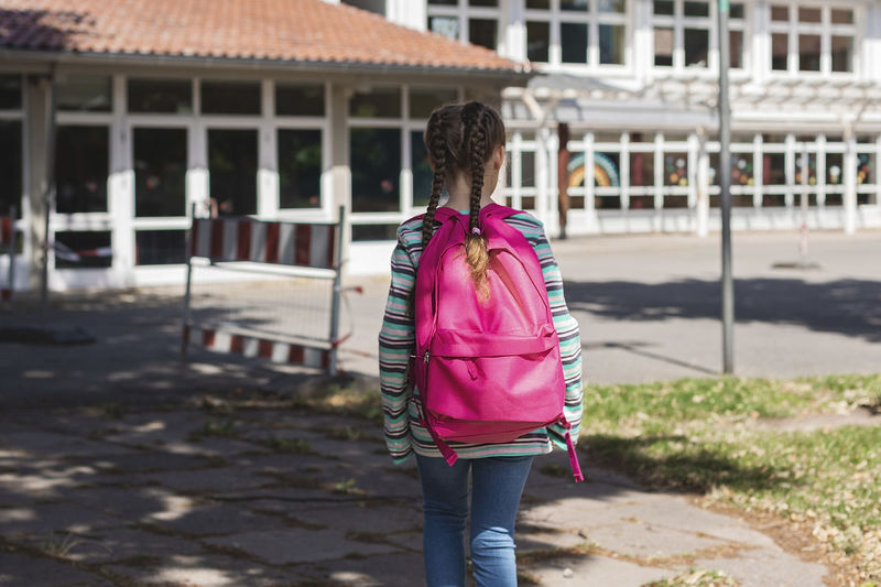 A girl with a pink satchel on her back approaches the school door. the first day of school.