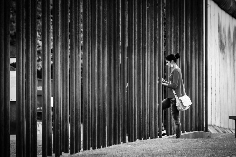 Side view of woman walking through fence
