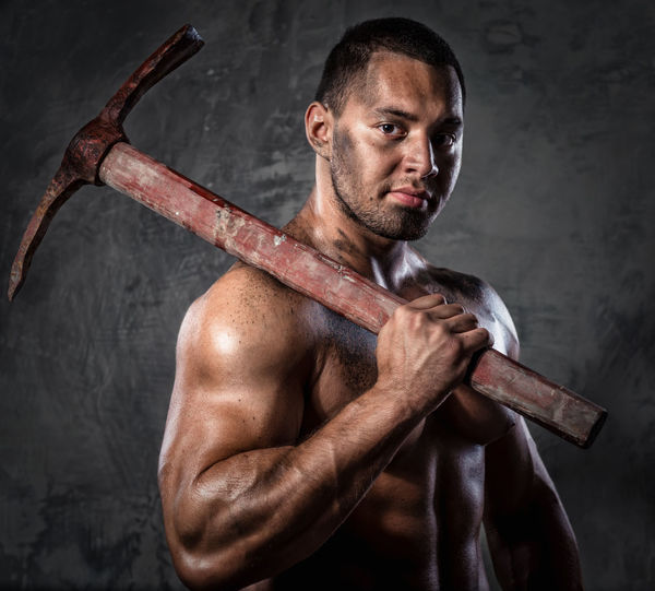 Portrait Of Shirtless Muscular Worker Holding Pick Axe Against Wall