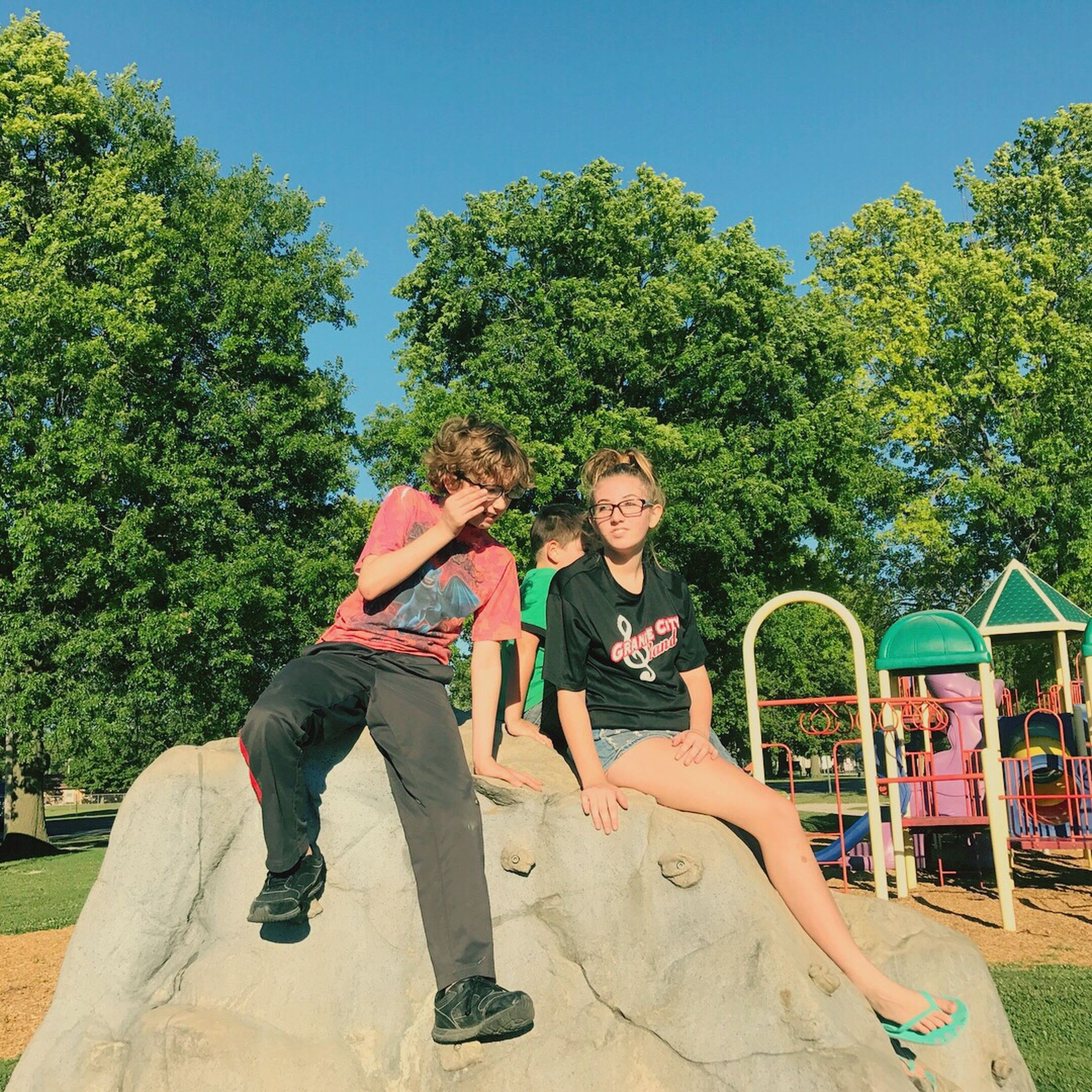 full length, leisure activity, tree, happiness, fun, smiling, casual clothing, young women, togetherness, day, two people, young adult, friendship, park - man made space, lifestyles, outdoors, young men, sitting, playing, sky, childhood, real people, people