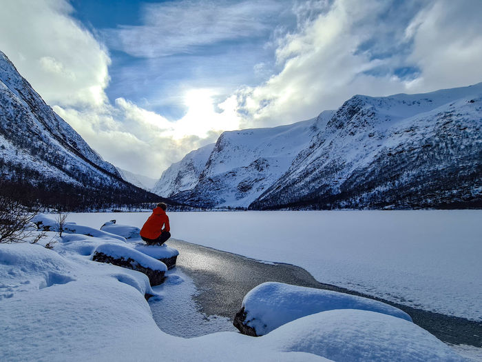 hiker and frozen lake against snow covered mountains