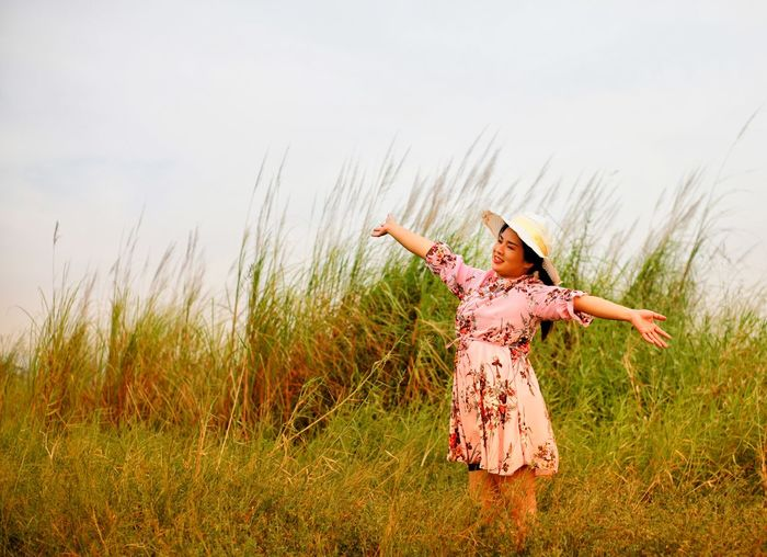 Woman with arms outstretched standing on field against sky