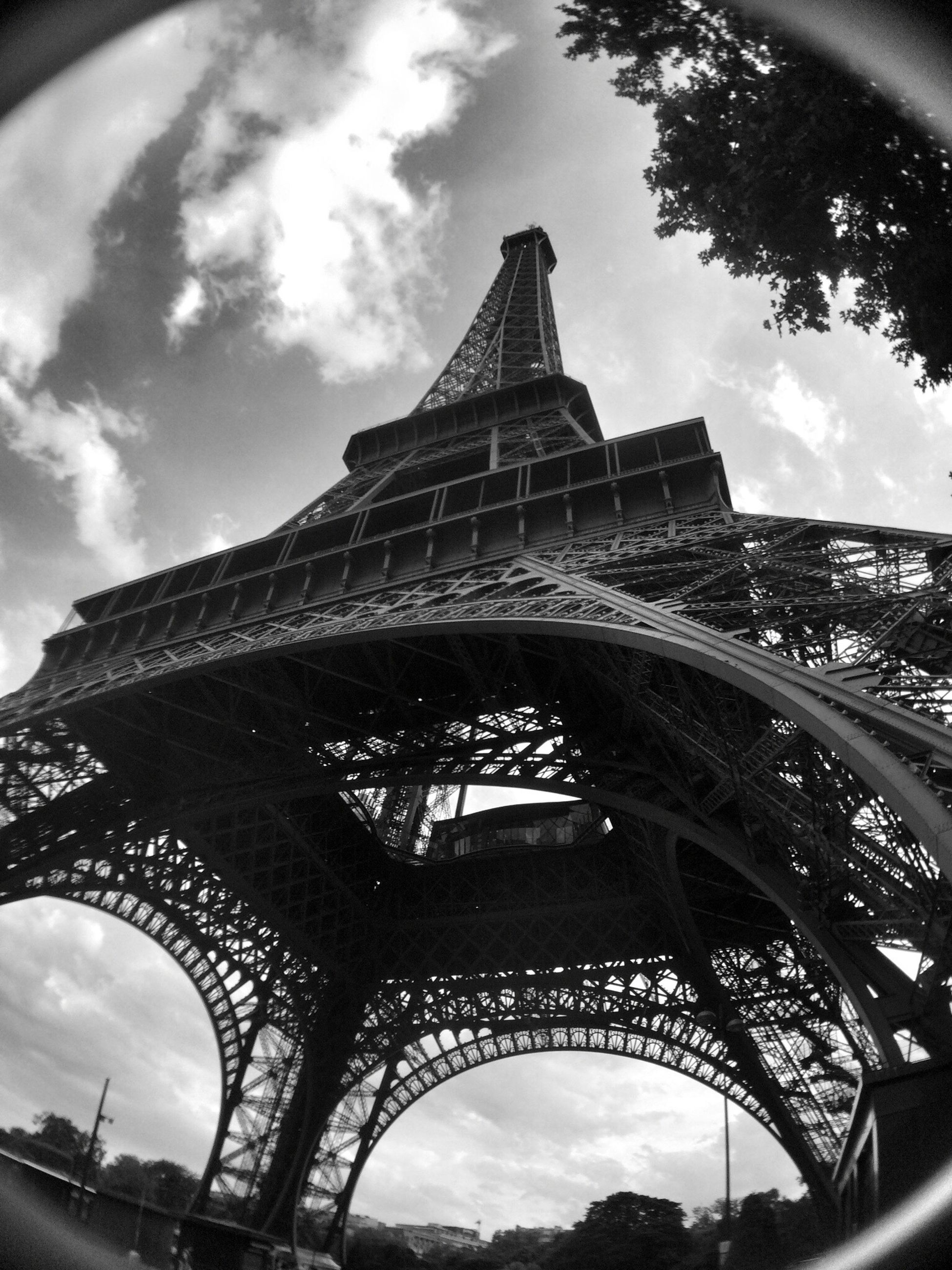 tourism, architecture, international landmark, travel destinations, low angle view, famous place, built structure, eiffel tower, capital cities, sky, culture, tower, travel, tall - high, arch, city, building exterior, tall, architectural feature, cloud - sky, history, iron - metal, outdoors, day, spire, vacations, 19th century style, majestic, city life, monument, cloudy