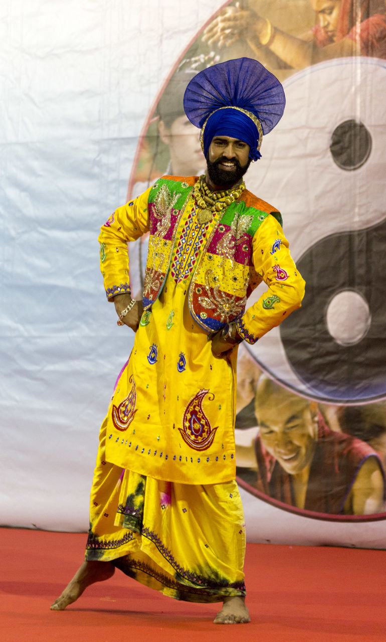 traditional clothing, yellow, cultures, real people, one person, full length, tradition, performance, turban, front view, men, standing, lifestyles, celebration, multi colored, day, headwear, performing arts event, sari, outdoors, powder paint, young adult, adult, people