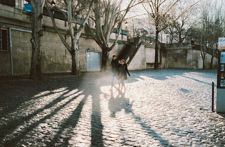 Architecture Bare Tree Building Building Exterior Built Structure City Day Footpath Full Length Lifestyles Nature One Person Outdoors Plant Real People Shadow Street Sunlight Tree