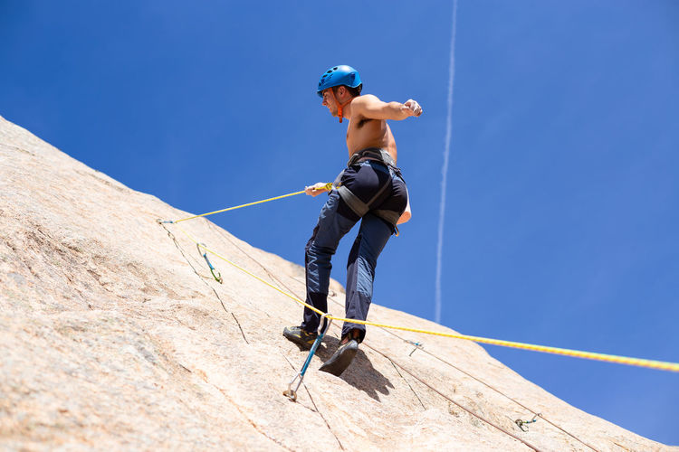 From below shot of shirtless male climber climbing mountain wall on amazing sunny day Man Climbing Climber Rock Cliff Sunny Daytime Shirtless Sport Mountain Extreme Sports Activity Height Rope Challenge Strong Adventure RISK Exercising Grip Young Adult Fearless Athlete Training Outdoors