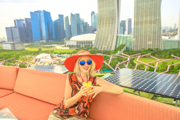 Lifestyle caucasian woman in wide hat drinking aperitif at rooftop cityscape skyline. Tourist enjoying above aerial view of Singapore marina. Travel holiday vacation in Singapore, Southeast Asia. Singapore Singapore City Woman Tourist Tourist Attraction  Tourist Destination People Girl Females Aerial View Skyline Cityscape Panorama Happy Travel Hat Lifestyle Enjoy Nature Tourism Smiling Aperitif Drink Orange Juice  Analcolic Glass One Person Architecture Built Structure Building Exterior Real People Leisure Activity Portrait Lifestyles Women Young Adult Day Fashion City Sitting Front View Sunglasses Looking At Camera Outdoors Tall - High Office Building Exterior Skyscraper
