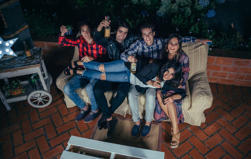 Happy young woman lying over group of friends on sofa in a outdoors party. Friendship and celebrations concept. Celebration Cocktail Friends Fun Happiness Happy Horizontal Lying Sitting Woman Young Alcohol Cheerful Drink Entertainment Friendship Group Group Of People Night Nightlife Outdoors Over Party People Sofa