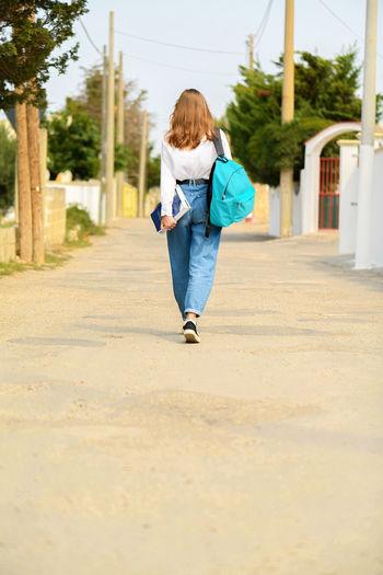 Rear view of girl walking on footpath in city