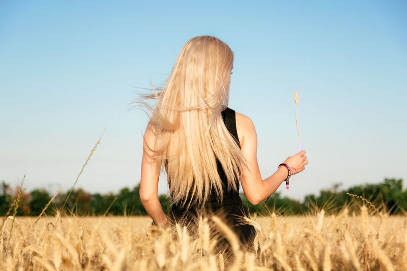 Rear view of woman standing in wheat field against clear sky