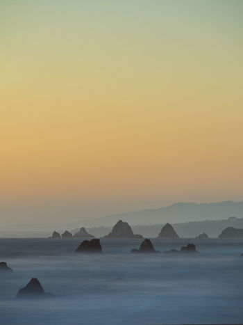 Long exposure sea stacks at Dillon Beach. Sky color gradient. Sky Scenics - Nature Sunset Water Beauty In Nature Tranquility Idyllic Sea No People Orange Color Clear Sky Rock Outdoors Headland Sea And Sky Sea Stack Longexposure Muted Colors Hazy  Layers Dillon Beach, CA