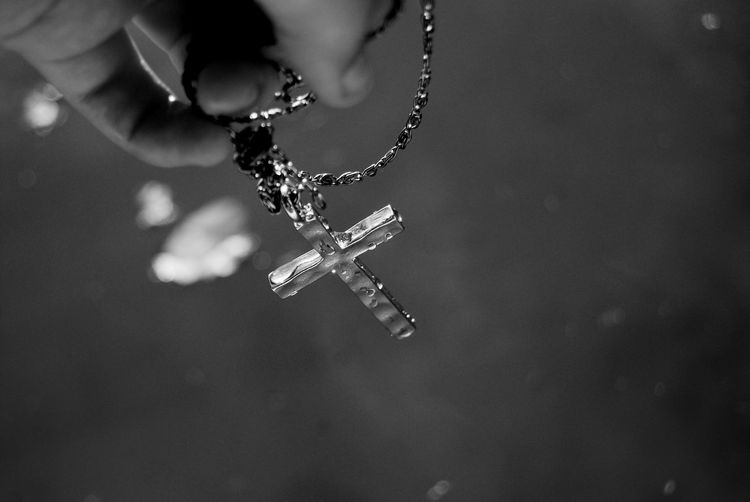 Close-Up Of Hand Holding Rosary Beads