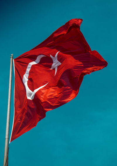 Low angle view of turkish flag against blue sky
