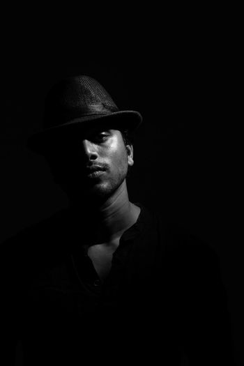 Portrait of young man wearing hat against black background