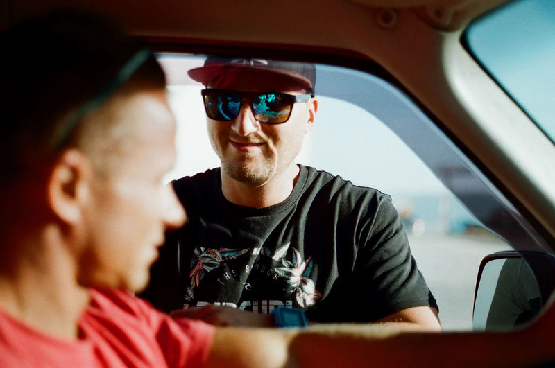 Smiling man looking at friend in car during sunny day