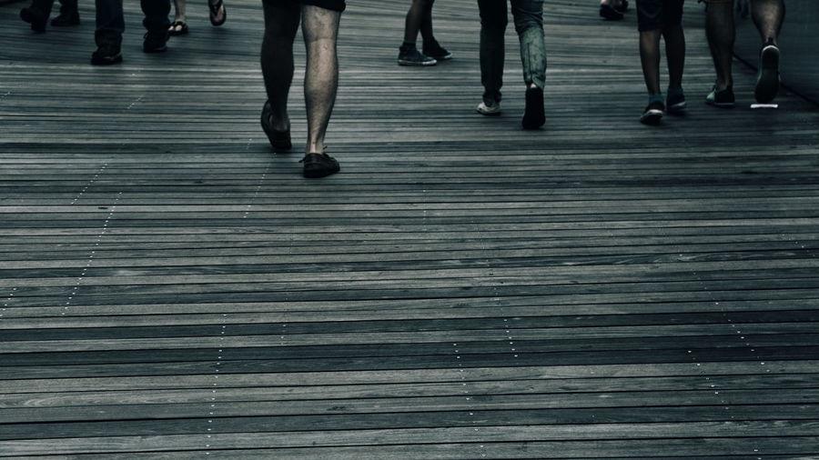 Low section of people walking on zebra crossing