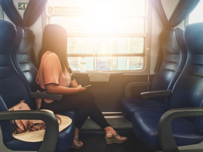 Looking out the window on a train. Mode Of Transportation Transportation Vehicle Interior Sitting Travel Women It's About The Journey Seat Journey Window Public Transportation Passenger Rail Transportation Land Vehicle Sunlight Train Vehicle Seat