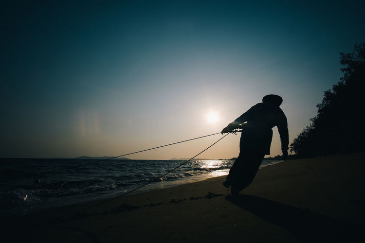 Beach Daily Life One Man Only One Person Outdoors People Real People Sand Sea Silhouette Sunset Working