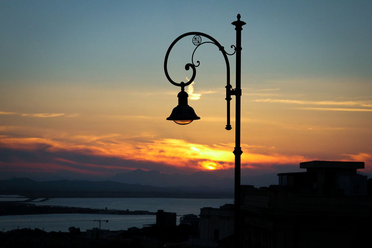Street light by silhouette buildings against sky at sunset