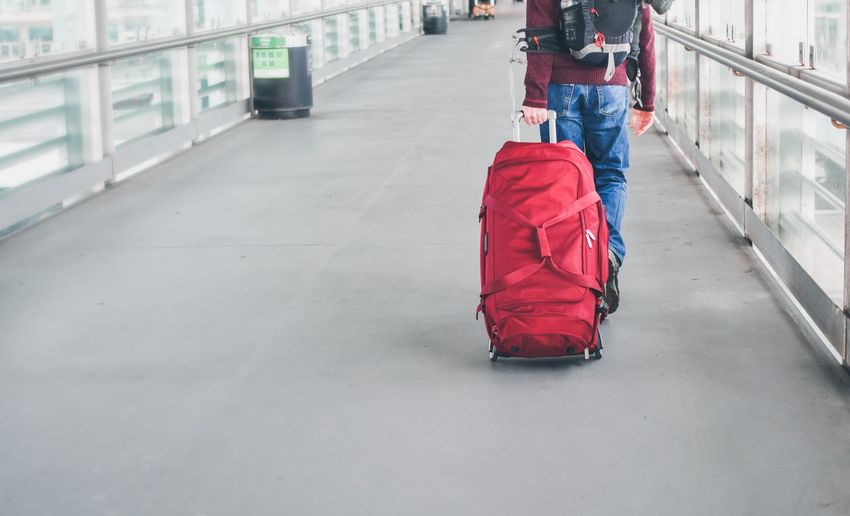 tourism man with red luggage in hand Man Outdoors Enjoying Life Vocation Trip Lifestyles person People Tourism Looking Fredom Baggage Walking Airport Transfer Transportation Journey Adventure Background Colour City Luggage Suitcase Men Red Airport Journey Winter Travel Passenger Transportation Building - Type Of Building Wheeled Luggage