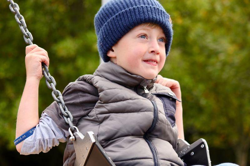 Smiling boy swinging outdoors