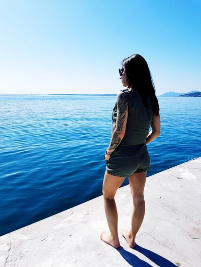 Full length of young woman standing at beach against clear blue sky
