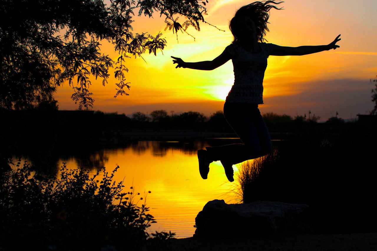 Full Length Of Silhouette Woman Jumping With Arms Outstretched By Lake At Sunset