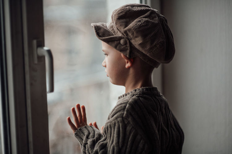 Side view of boy looking at window