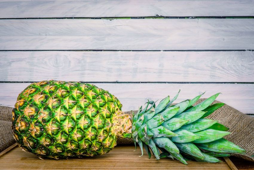 Pineapple on a wooden board Exotic Wooden Kitchen Food Tropical Fruit Pineapple Wood - Material Green Color Table No People Indoors  Day Nature Close-up