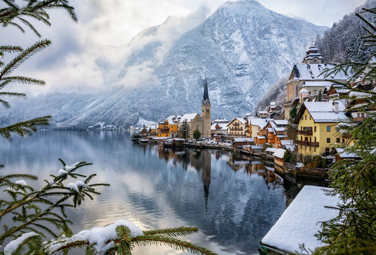 Scenic view of lake by buildings and snowcapped mountains during winter