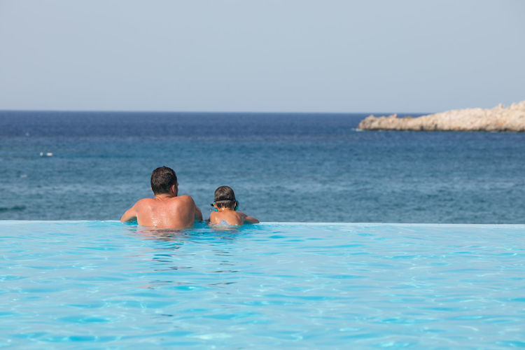 Rear view of father and son in infinity pool against sky