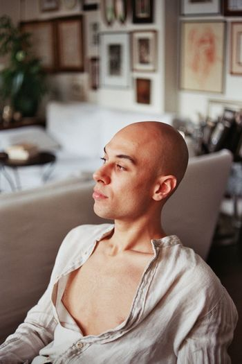 Thoughtful bald young man looking away while sitting at home
