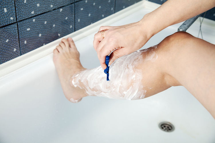 Low section of woman shaving leg in bathroom at home