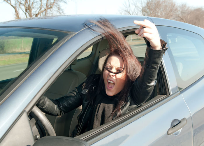 angry woman in car Angry Displeased Driving Stress Woman Anger Annoyed Car Conflict Day Driving Frustration Furious Gesturing Middle Finger Mouth Open One Person Real People Screaming Shouting Young Adult Young Women
