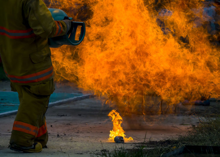 Midsection of man extinguishing fire