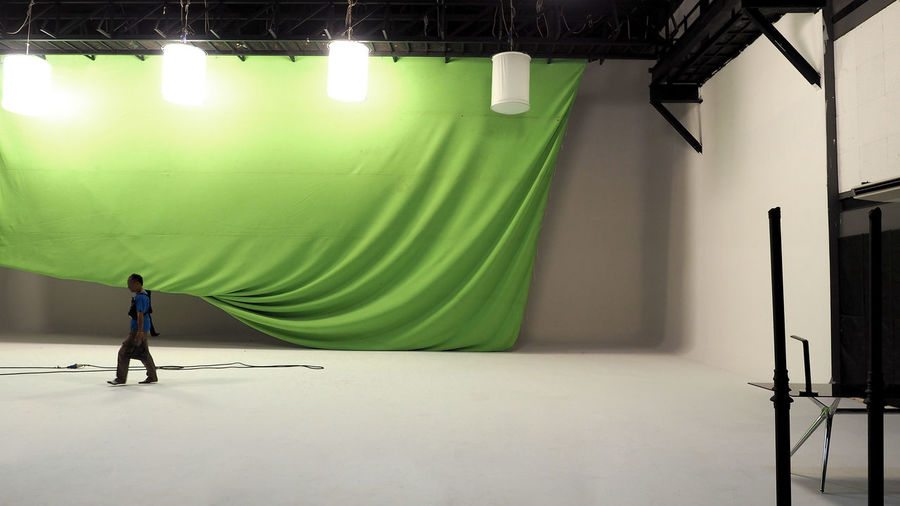 Big studio with green screen and lightman and soft box light hanging and white floor. Day Green Green; Studio; Screen; Photography; Chroma; Film; Empty; Key; Background; Light; Backdrop; Photo; Modern; White; Object; Space; Technology; Equipment; Professional; Room; Soft; Tool; Floor; Place; Stand; Crew; Lightman; Lamp; Illuminated; Electrical; Trip Illuminated Indoors  Light One Person People Real People Screen Studio