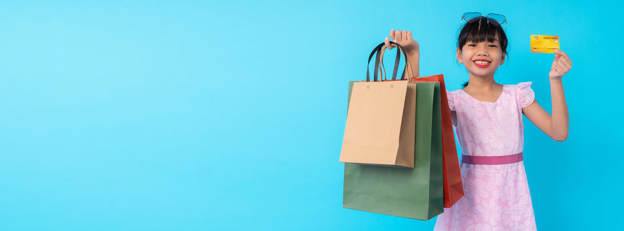 Portrait of cute girl holding credit card while holding shopping bag against blue background