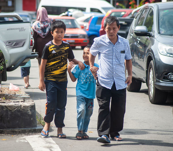 Rear view of boys standing on road in city