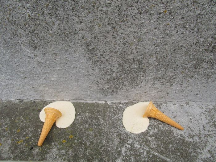 Melted ice cream cone discarded on pavement