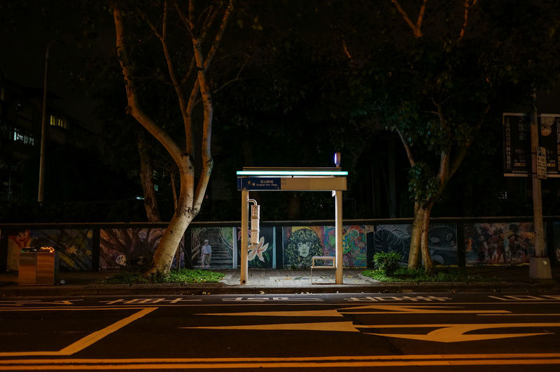 Illuminated Bus Shelter At Sidewalk In City
