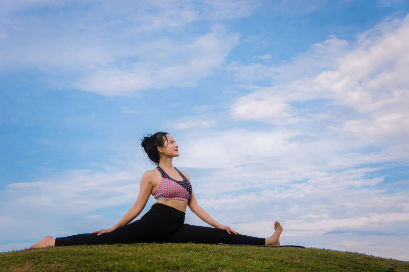 Side view of woman doing yoga on grassy field against cloudy sky