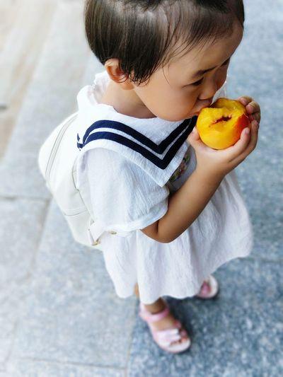 High angle view of girl eating peach