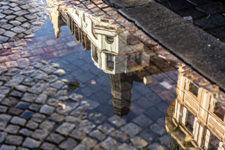 Buildings reflecting in puddle