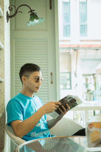Activity Boys Casual Clothing Child Day Holding Indoors  Leisure Activity Lifestyles Males  Men One Person Reading Real People Sitting Table Waist Up Window My Best Travel Photo