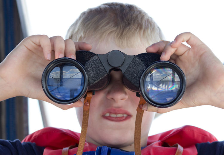 Close-up portrait of boy holding sunglasses