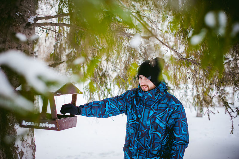 Portrait of young man standing by bird feeder on tree during winter