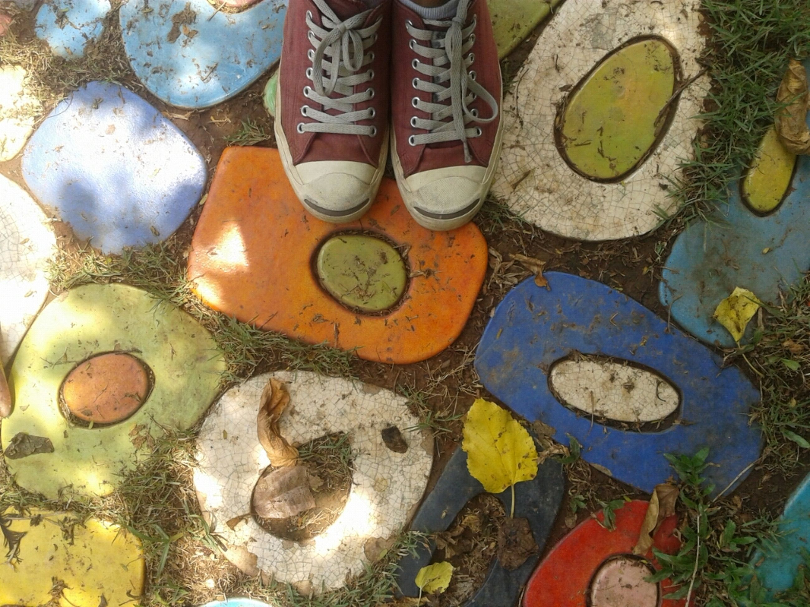 high angle view, variation, large group of objects, abundance, directly above, shoe, text, still life, close-up, outdoors, choice, day, no people, yellow, stone - object, multi colored, arrangement, number, for sale, western script