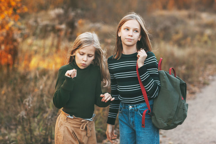The two sisters return from school and talk as they drive through an open-air autumn park.