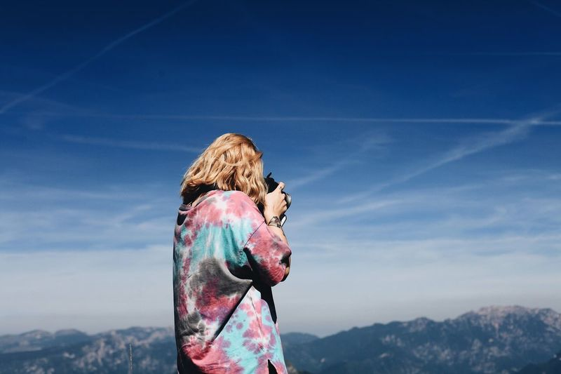 Rear View Of Woman Photographing Against Blue Sky
