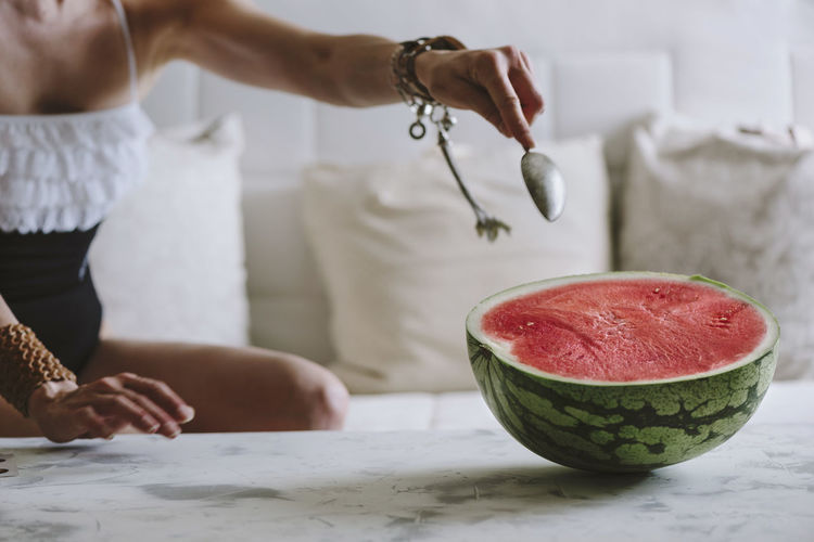 Midsection of woman eating watermelon on table
